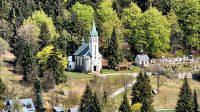 Pohled na kostel sv. Antonína Paduánského a místní hřbitov ze zelené turistické značky nad sjezdovkami